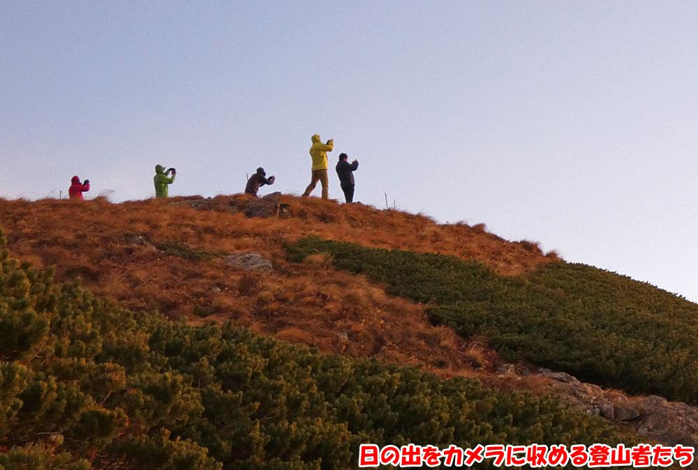 日の出をカメラに収める登山者たち